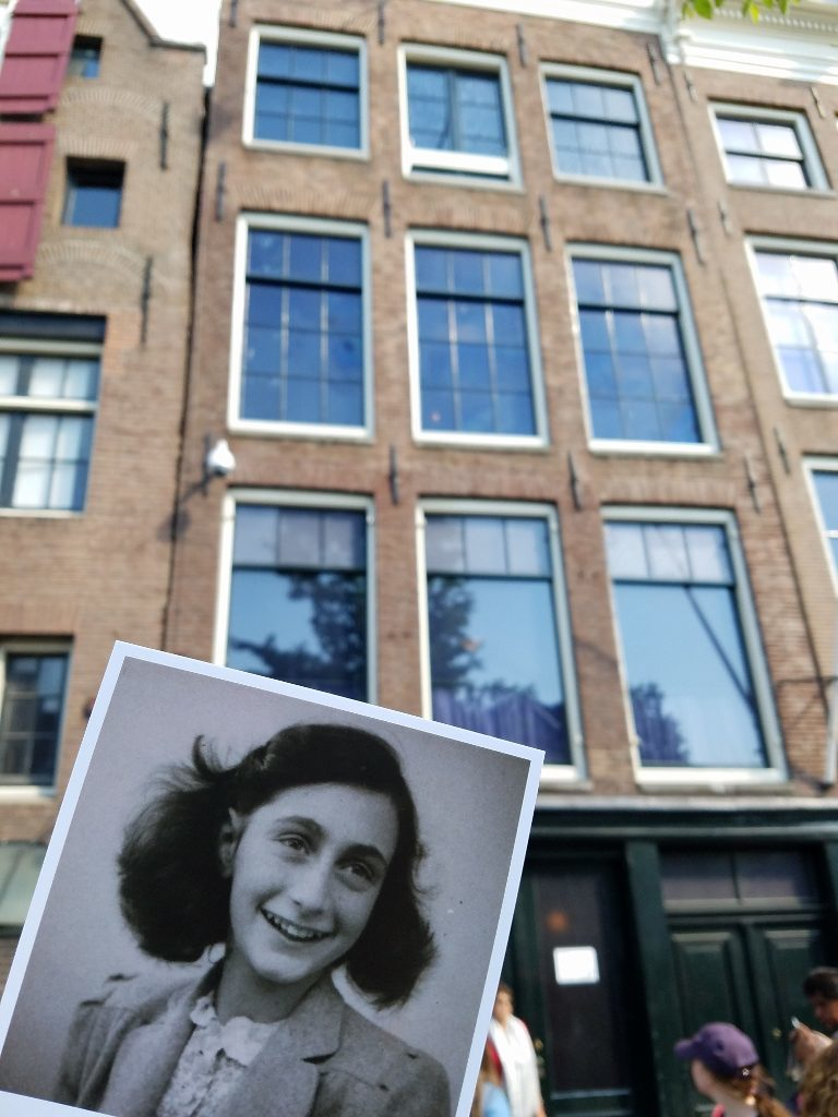 Postcard of Anne Frank in front of the house